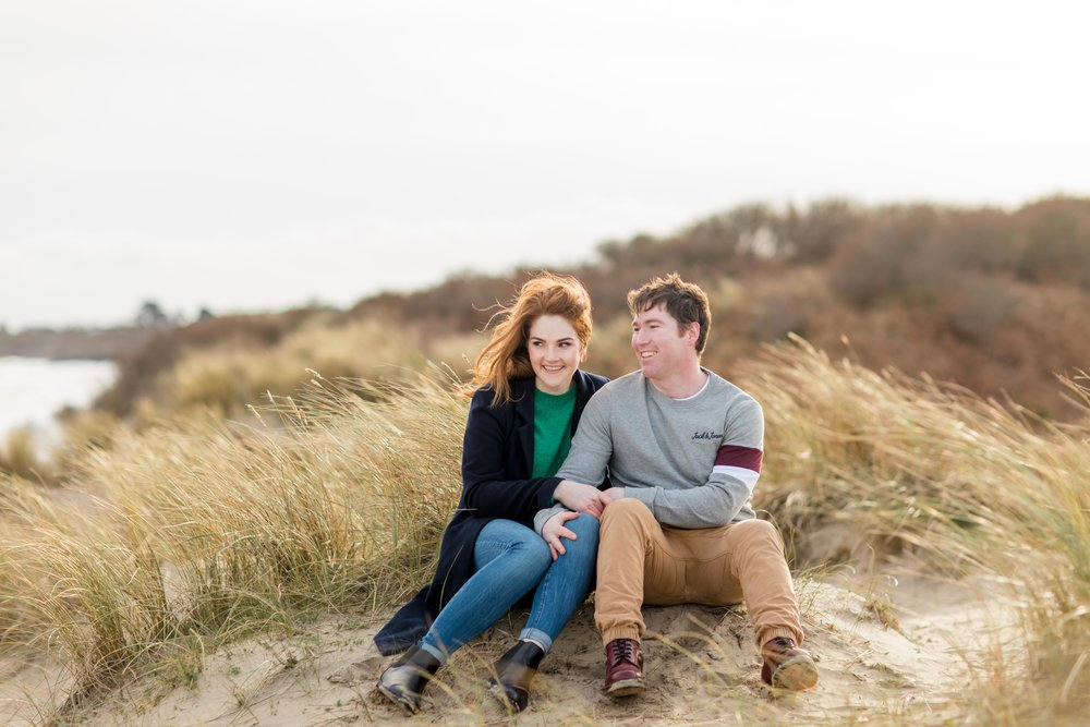 a couple sitting on a sand dune smiling into the distance dressed in late winter clothes covered in a golden sunset posing for their engagement photoshoot in ireland on brittas bay