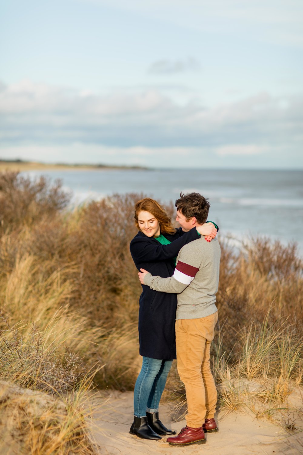 a couple standing on a grassy sand dune with their hands wrapped around each wearing black coat blue jeans black ankle boots and khaki chinos with brown ankle boots