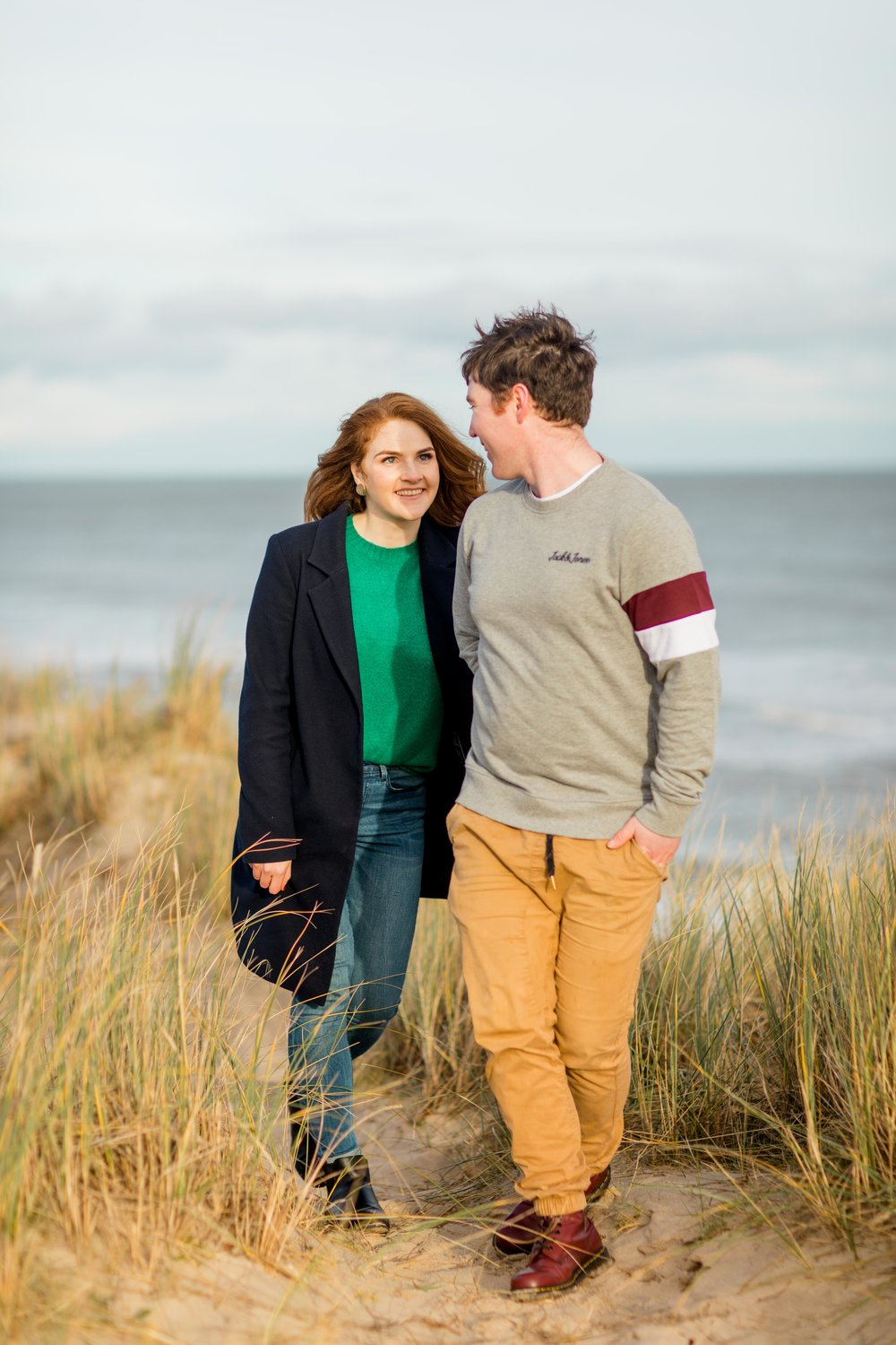 an engaged couple walking on a sandy beach in ireland brittas bay holding hands smiling looking at each other wearing a black knee length coat and khaki chinos