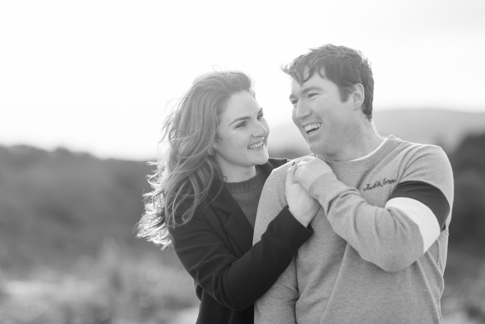 a couple smiling posing for a photoshoot wearing black coat shoulder length wavy hair and a mens grey jumper