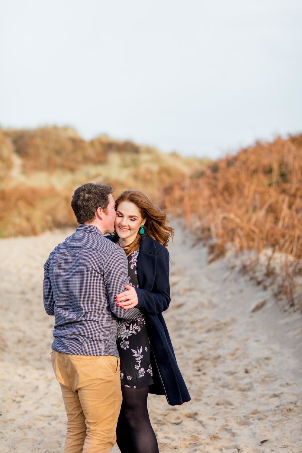 a couple posing for an engagement shoot wearing a black checkered shirt with khaki chinos and a knee length black dress with white flowers and green earings
