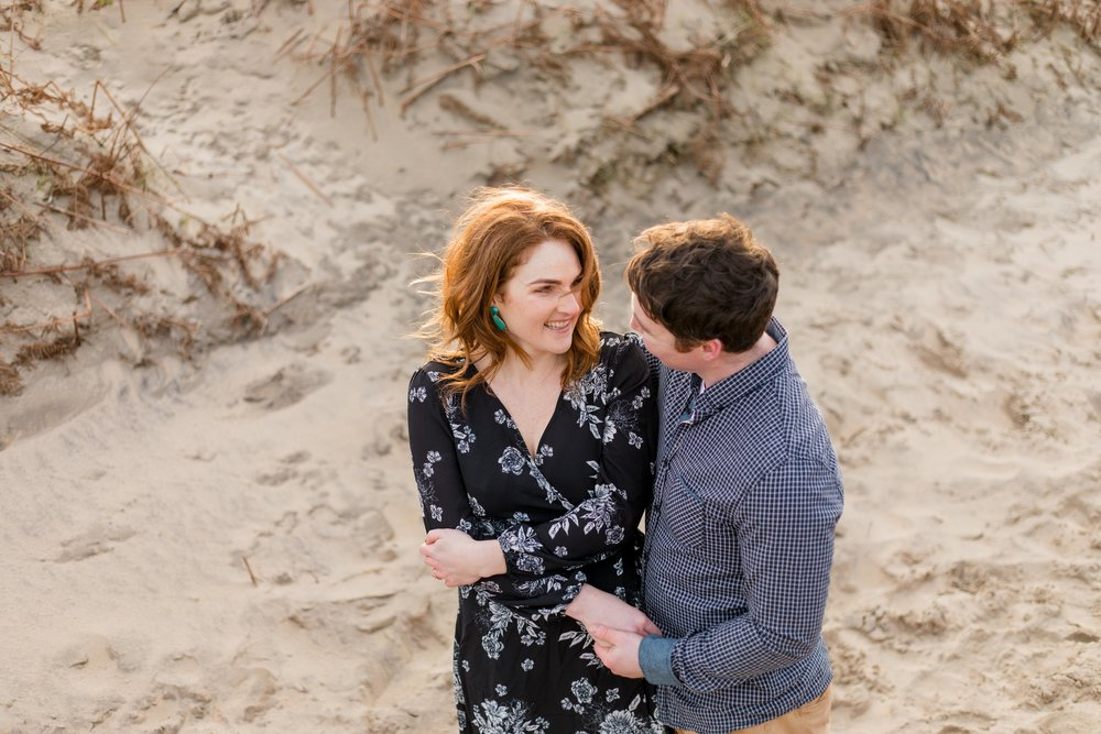 a woman wearing a black dress with white roses on it and green earrings complementing her red hair is smiling at her future husband at her engagement session on an irish sandy beach