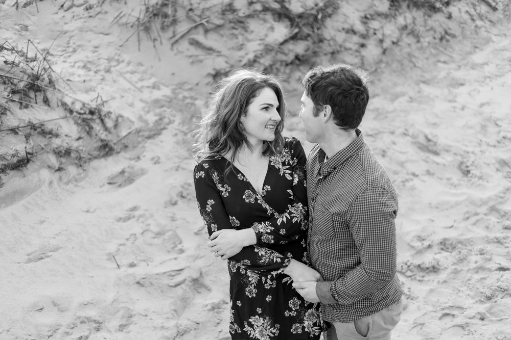 a black and white photo of a woman and a man posing for an engagement photoshoot holding hands wearing black and white clothes with pattern on it located in ireland