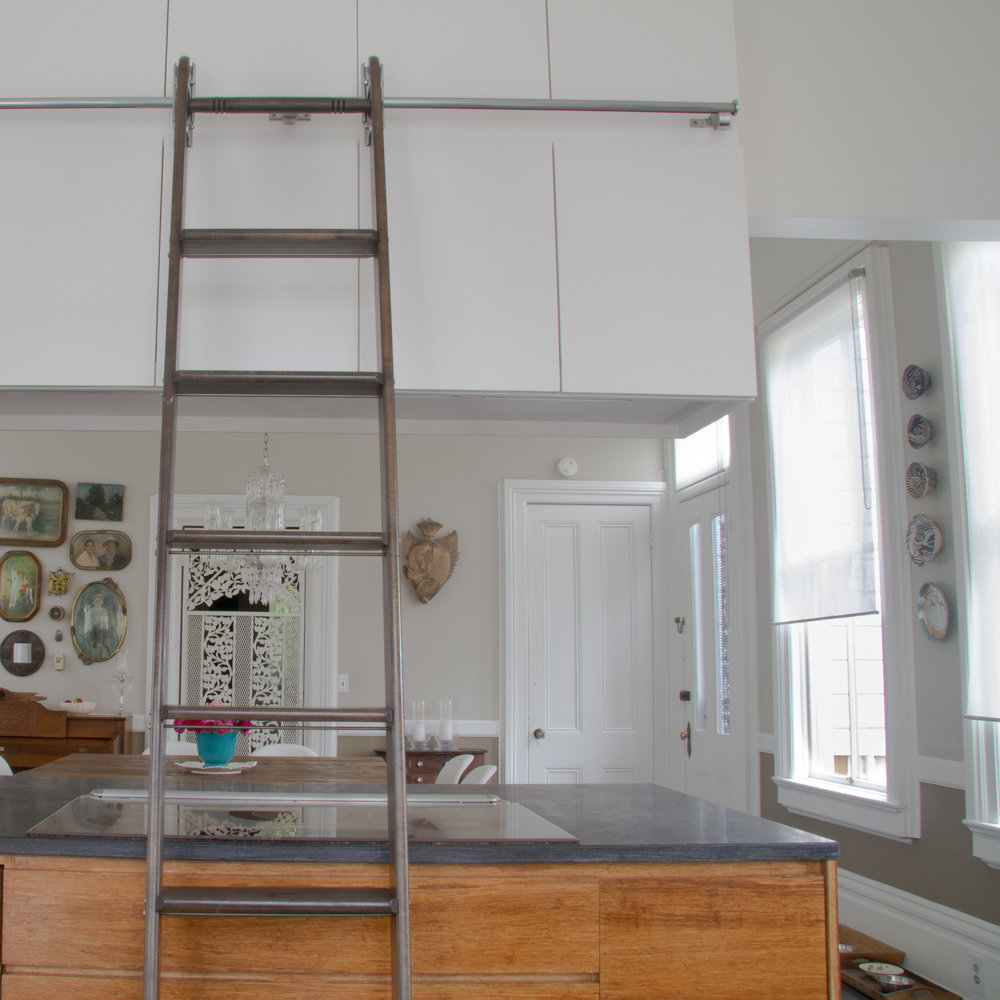 (4/21) The upper kitchen cabinets are accessed by a library ladder which hooks onto a rail that runs around the room.