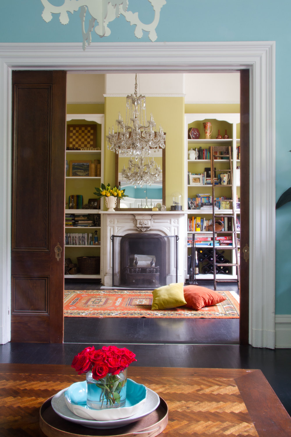 (8/21) The library's original pocket doors are one of Lock's favorite details in the house, as is the frequently-used fireplace. The bright blue living room walls in the foreground are painted in  Benjamin Moore  How Blue Am I.