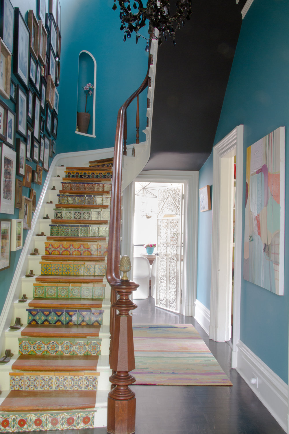(14/21) Lock tiled the stair risers herself, and it was a labor of love. The bright blue wallcolor is  Benjamin Moore 754 Wilmington Spruce, and the dark grey stair underside is done in a color called French Beret.
