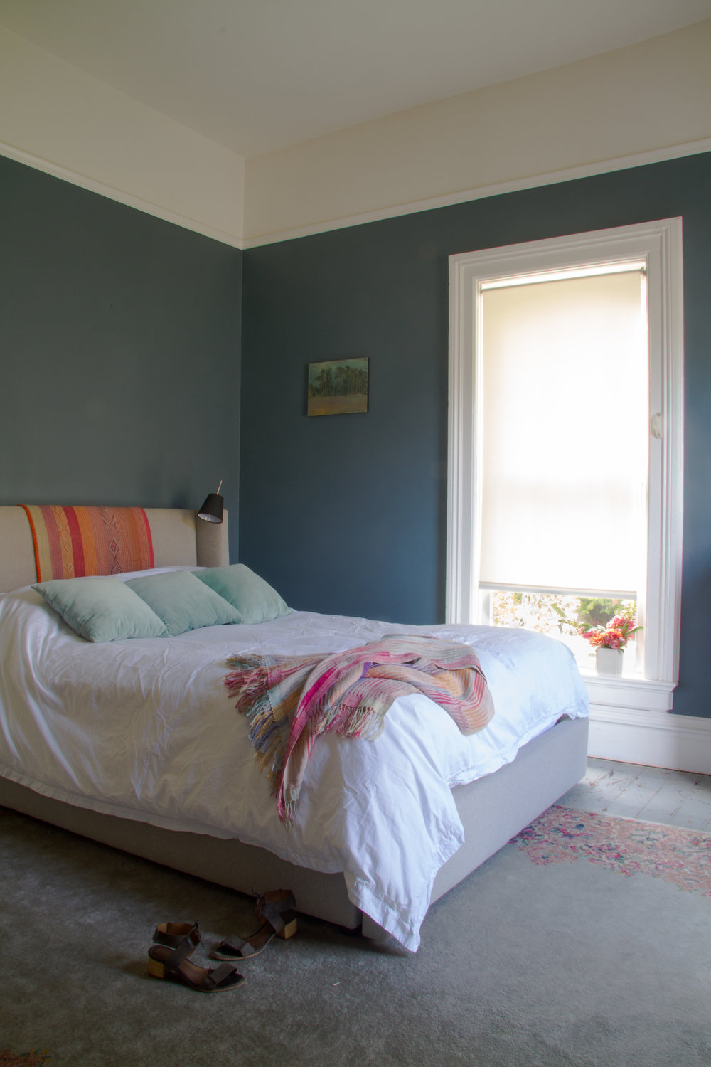 (16/21) A Peruvian throw over the master bedroom headborad is from Lock's store, as is the woven one. The painting was her first of many by local artist  Brian Rounds . Walls are  Benjamin Moore  Blue Dusk.