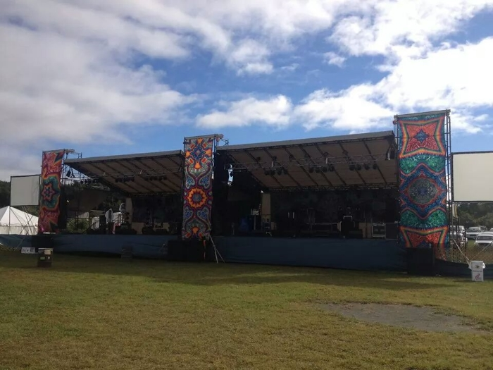 Here is our festival stage. Each side is 33' wide x 24' deep. Monitor world is 10' x 10' in the center. We typically fly 8 line array per tower. {The banners are not included}