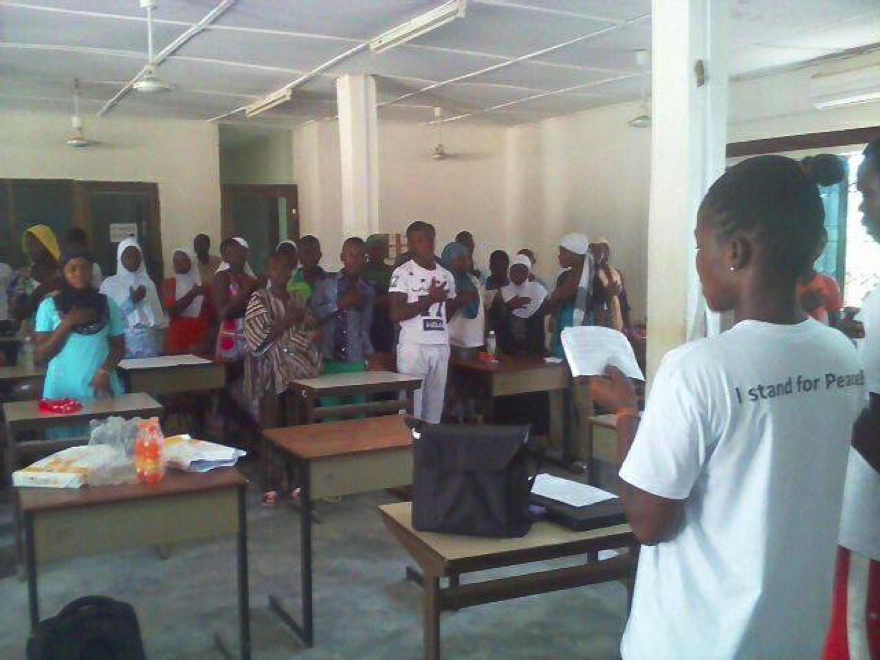 A Young Peace Ambassador administering the peace pledge to a group of young people