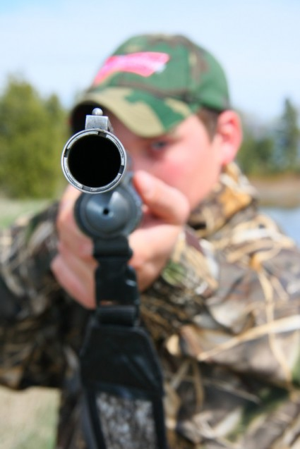 Senior portrait Luke aiming shotgun at camera