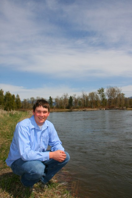 Senior portrait Luke in blue shirt by river
