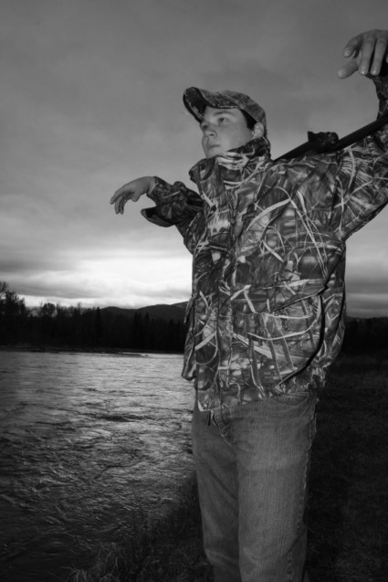 Senior portrait Luke with shotgun by river