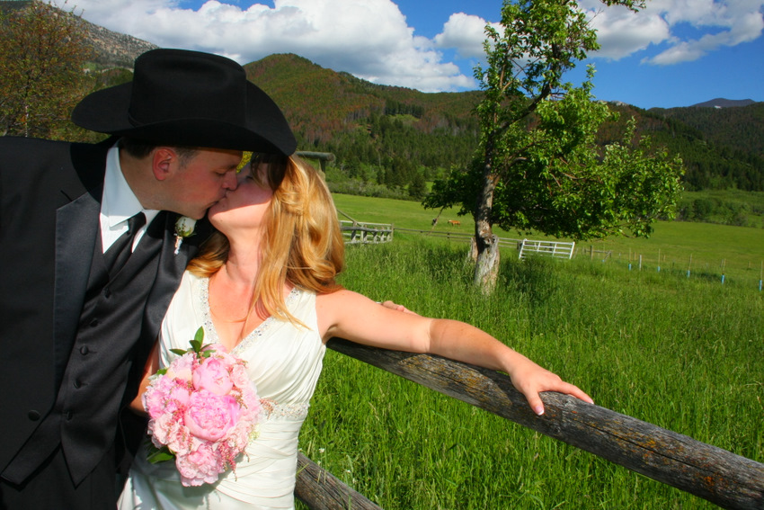 Bride and groom kissing by fence cowboy