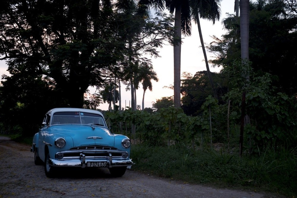 Antique car parked at a country road in El Cotorro, Cuba