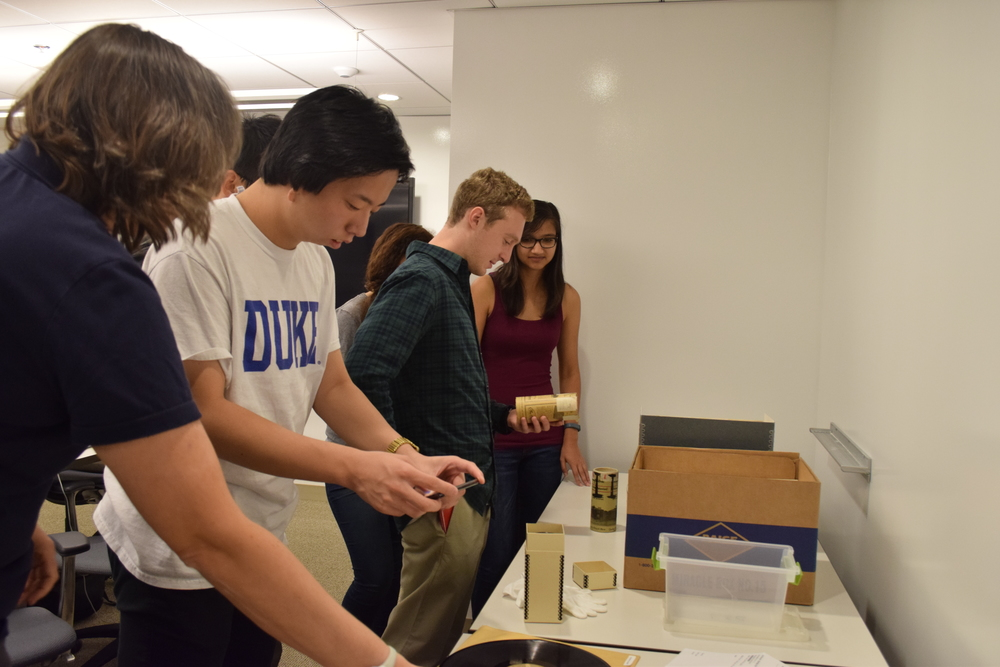 Students examining wax cylinders and glass disks