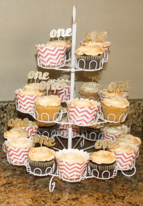 "Coral chevron wrappers with gold glitter ""one"" toppers with  The Petite Cakery's  amazing cupcakes!"