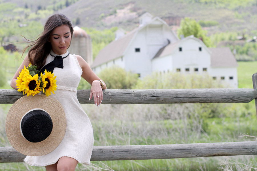 Zara Look with sunflowers. White McPolin Barn in Park City on the background.