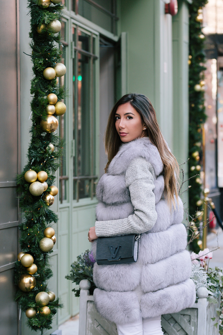 Ulia Ali wearing fur vest and Louis Vuitton bag.