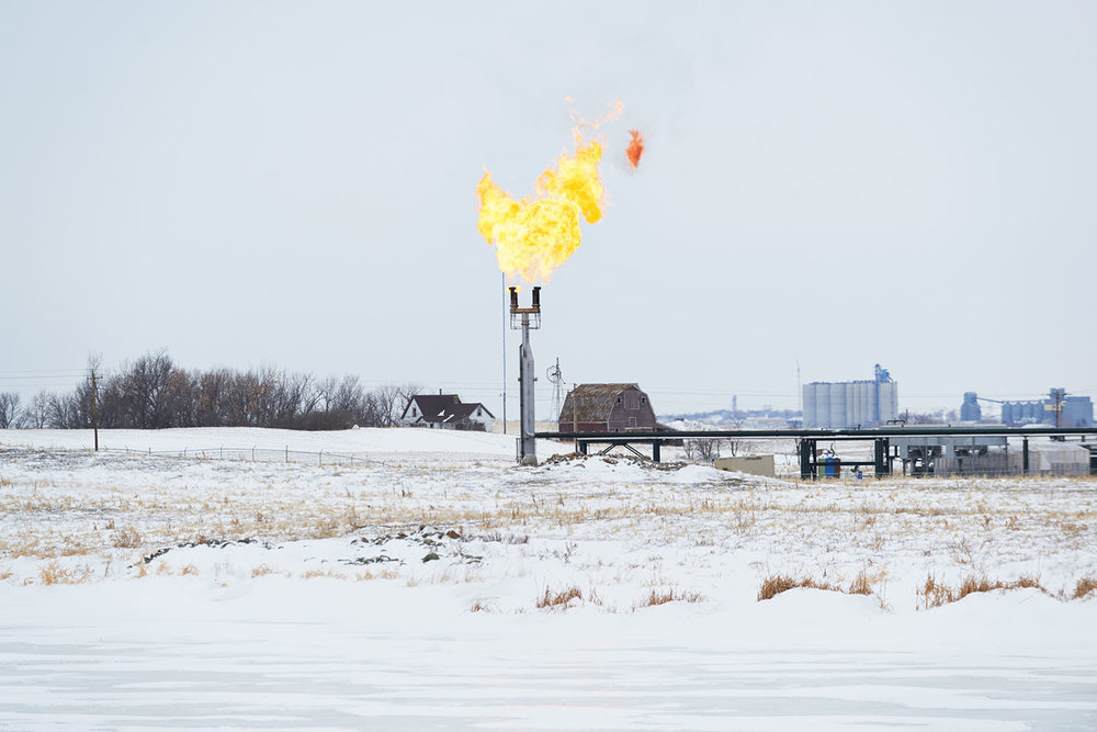 Drillers burn off the natural gas that surfaces with oil on a farm in North Dakota