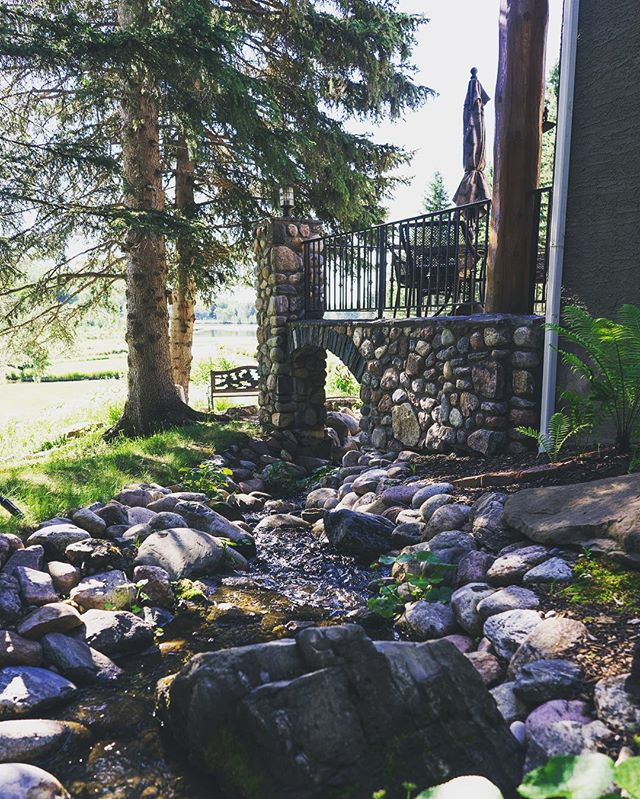 The little details always make spectacular features. This creek was designed to flow through the rock work of the deck.  Landscape Architectural Consulting Construction and Design. Phone: 1-403-949-2785  scopeprojects.com  #lakehouse #privatelake #privatelakehouse #reflection #luxuryhomes #braggcreek #mansiononthewater #luxuryhome #waterlovers #rockwalls #dreamdeck