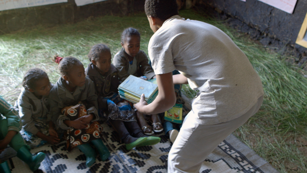 18-year-old Belihu hands out local language books to children during story reading time at the Mishig reading camp. (Photo credit: Max Greenstein / World Vision)