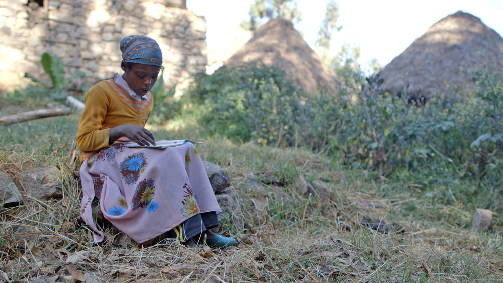 """Before the reading camp, Seble's reading skill level was low,"" says her grandfather, 62-year-old Gebrehana. ""She struggled to read sentences and understand complex statements. Now she's performing better at school."" (Photo credit: Max Greenstein / World Vision)"
