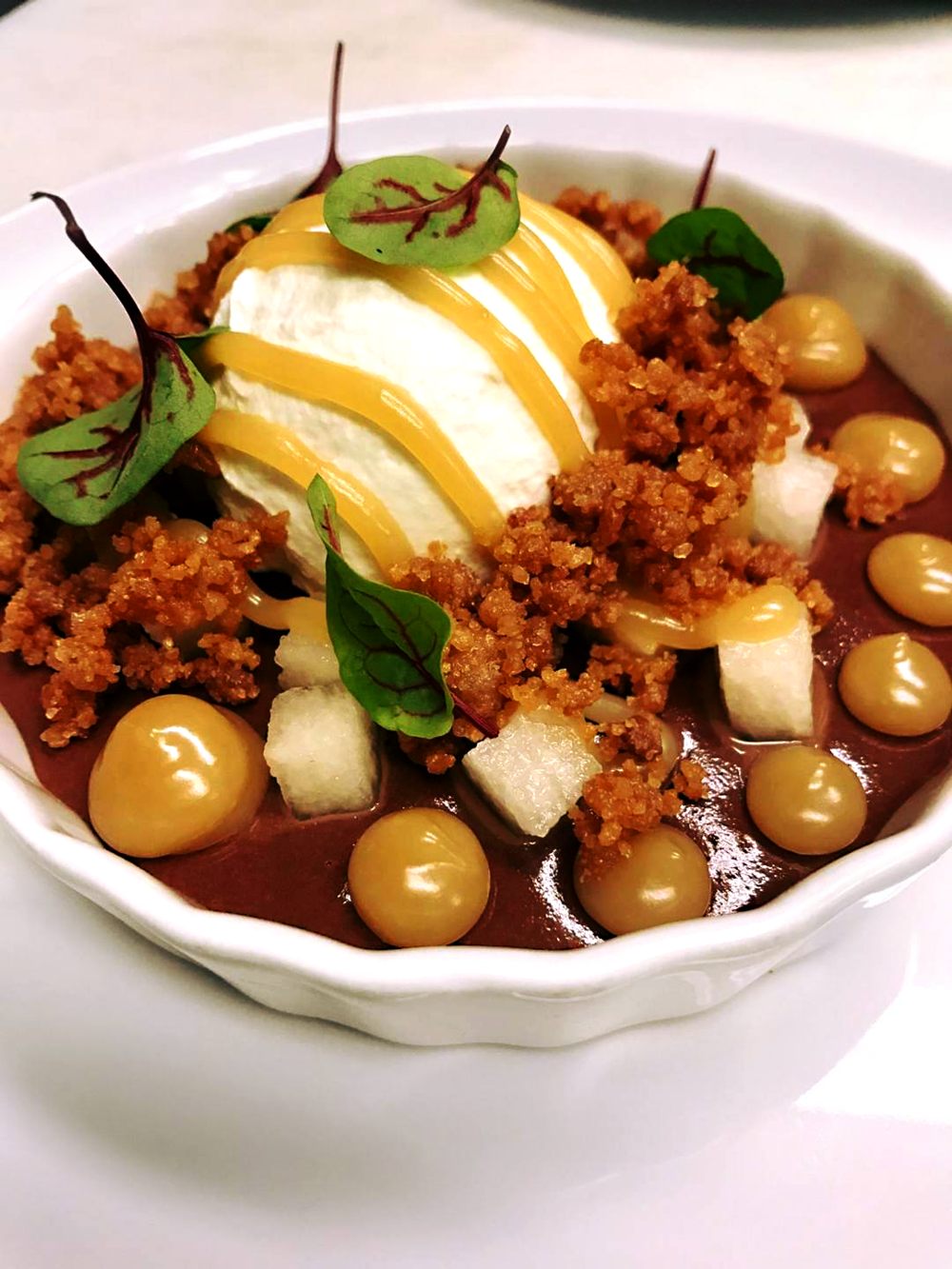 Dark Chocolate Pudding  accompanied by a Bourbon poached pear, caramel sauce, streusel, and whipped cream.