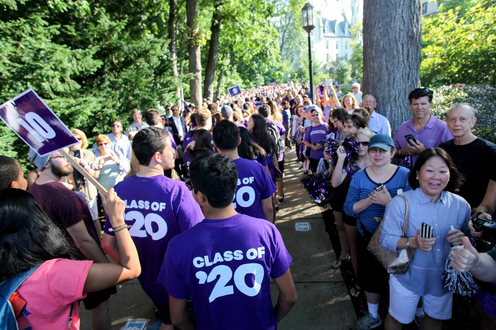 "New students ""March Through the Arch"" as families, staff, and faculty cheer on."