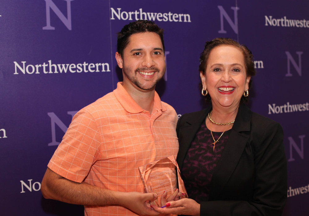 Alejandro Magaña of Multicultural Student Affairs accepts the Distinguished Service Award from Vice President for Student Affairs Patricia Telles-Irvin.