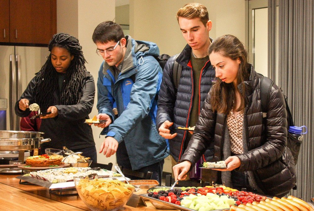 Students dig into food at the gallery opening.
