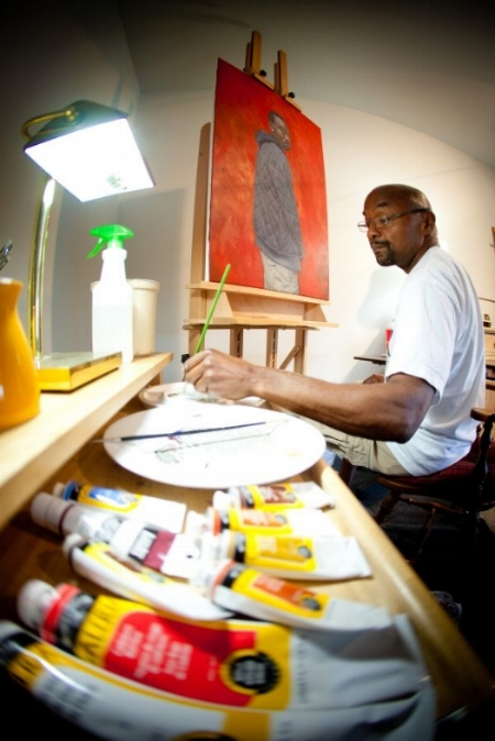 RIcardo Lewis painting in his studio
