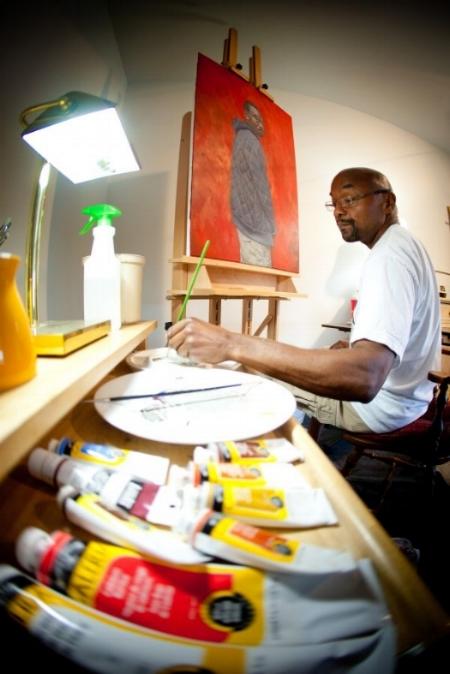 RIcardo Lewis painting in his studio