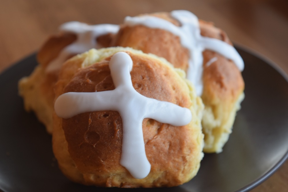 Pre-order traditional hot cross buns, available in six packs. Soft dinner rolls with currants and sweet crosses over each roll, contains dairy.