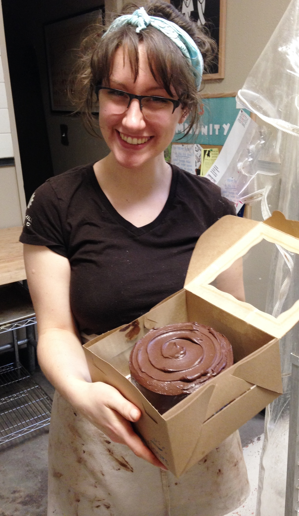 Katie with the first Paleo cake she frosted at the bakery!