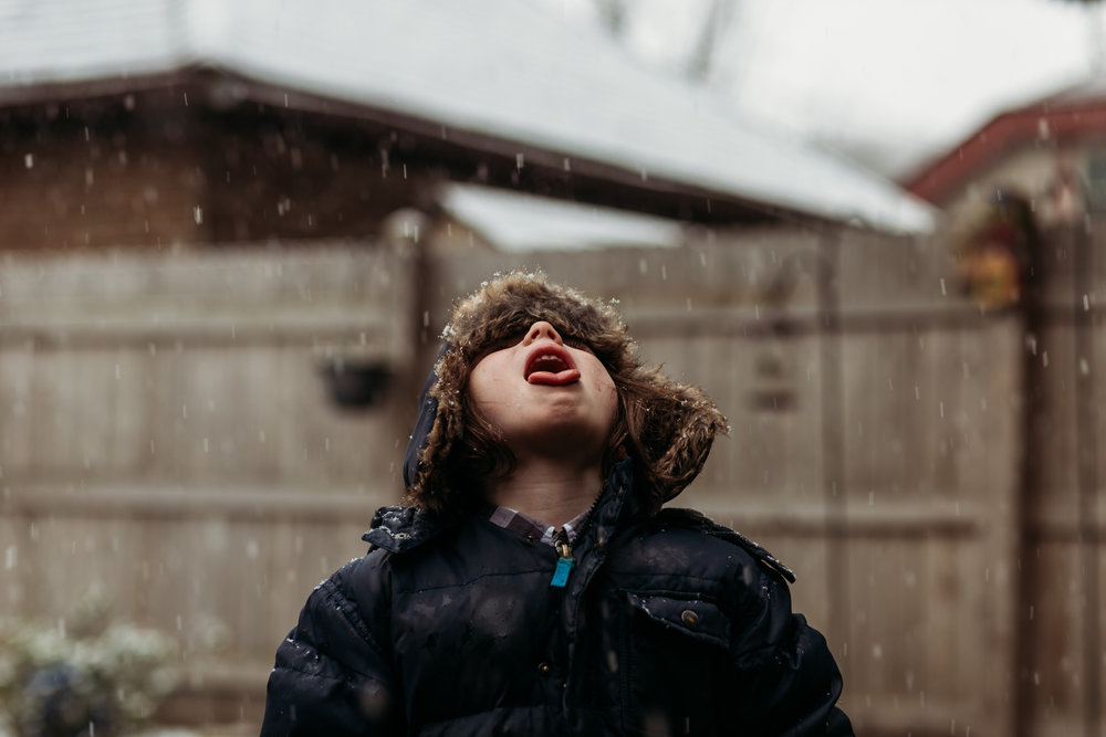 My son catching falling snow flakes. See the neighbor's garage?