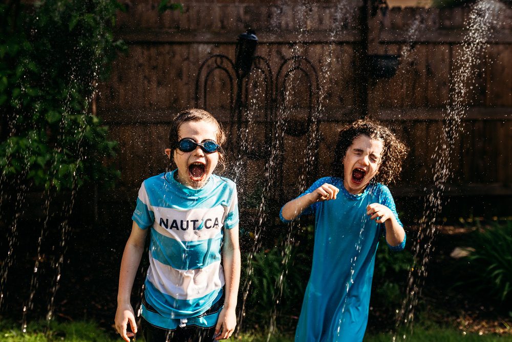 Children running through the sprinkler and drinking the water