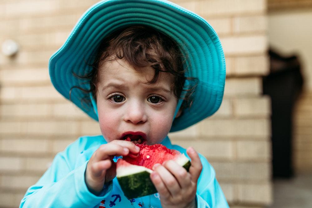 Little boy in bathing suit eating watermelon