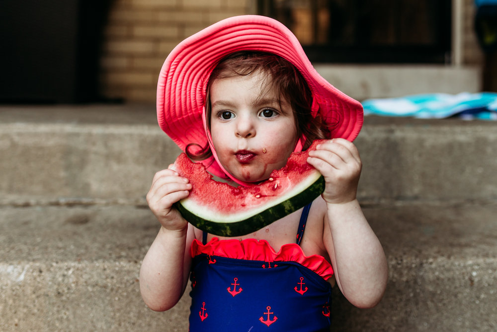 Little girl eating watermelon in a bathing suit.