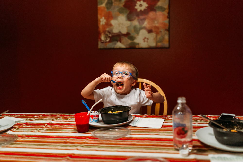 Little boy making a goofy face while eating his dinner