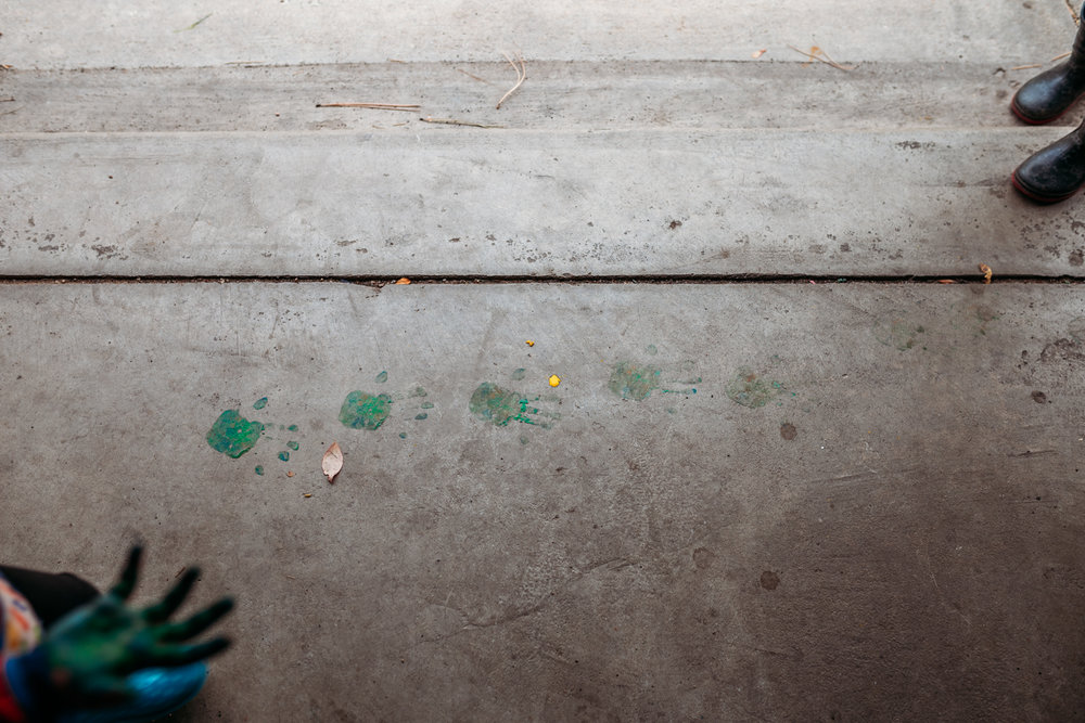 "Little girl's painted hands in bottom left hand corner of image, with painted handprints on concrete ""walking across"" to top left corner with brother's boots."