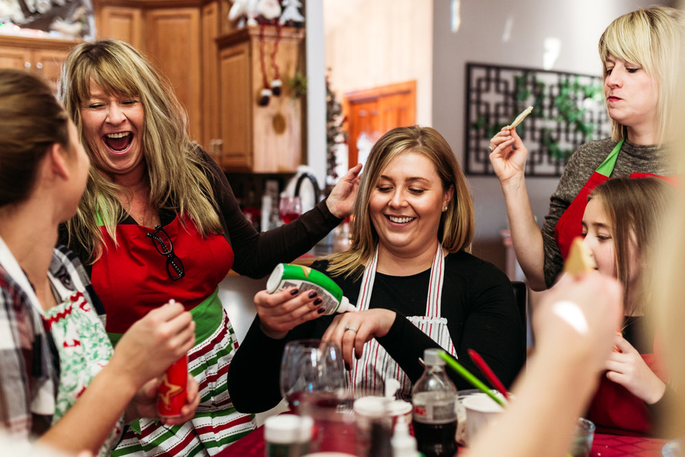 Women family laughing while decorating holiday cookies
