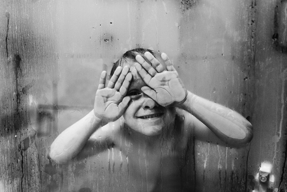 Little boy pressing his face and hands on the shower door