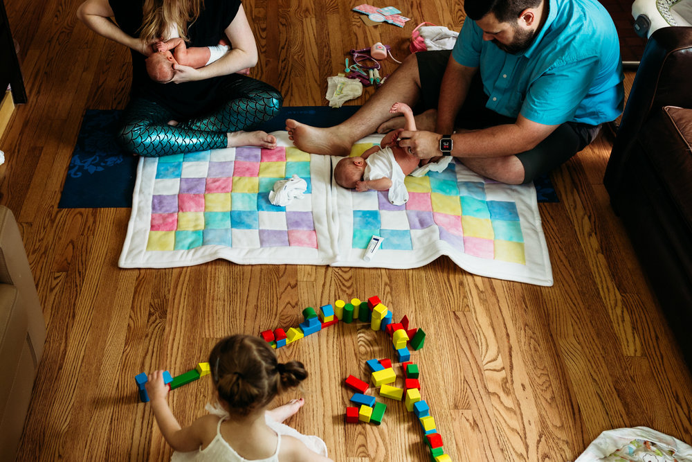 Parents sitting on the floor holding and feeding newborn twins, while toddler daughter plays with toys nearby