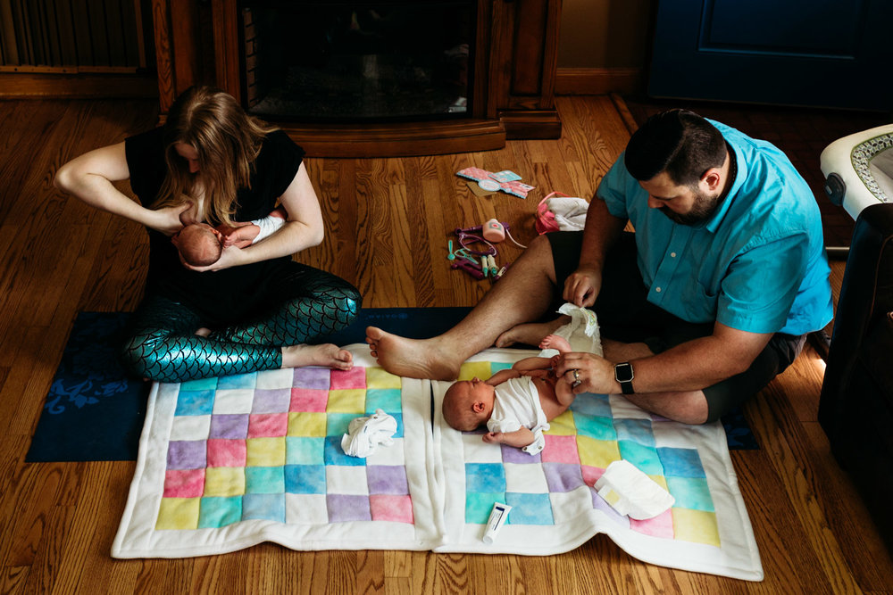 Mom breastfeeding and dad changing a diaper on newborn twin boys in Milwaukee