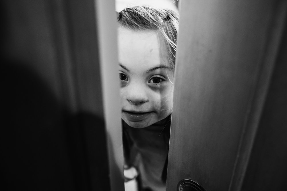 Little girl with down syndrome peeking through her door