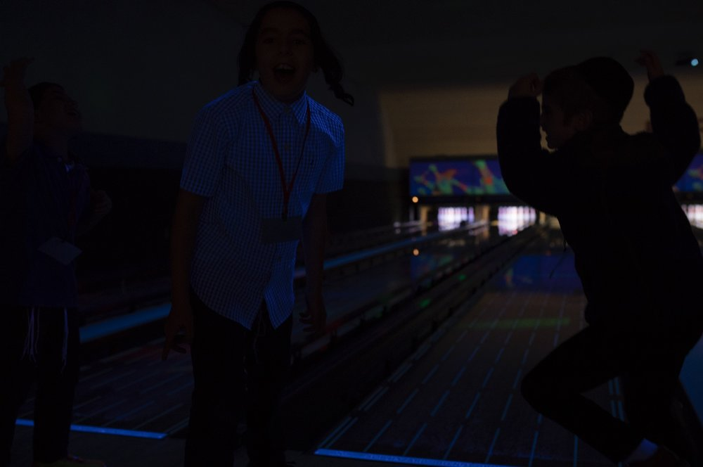 Unedited photo of 3 boys at a bowling alley
