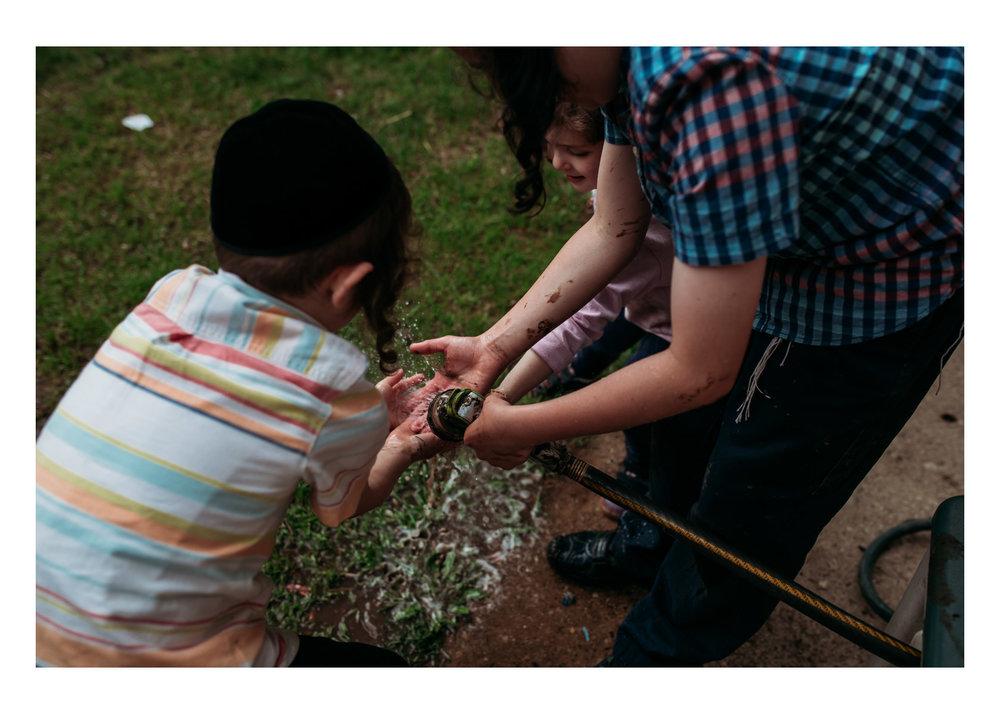 3 children washing mud off their hands with a garden hose in Milwaukee Wisconsin