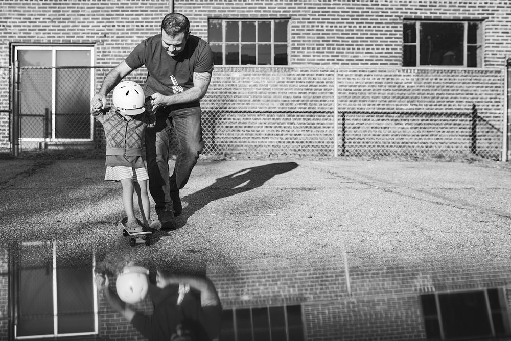 Manhattan, Kansas based documentary family photographer snaps a picture of a dad teaching his daughter how to skateboard.