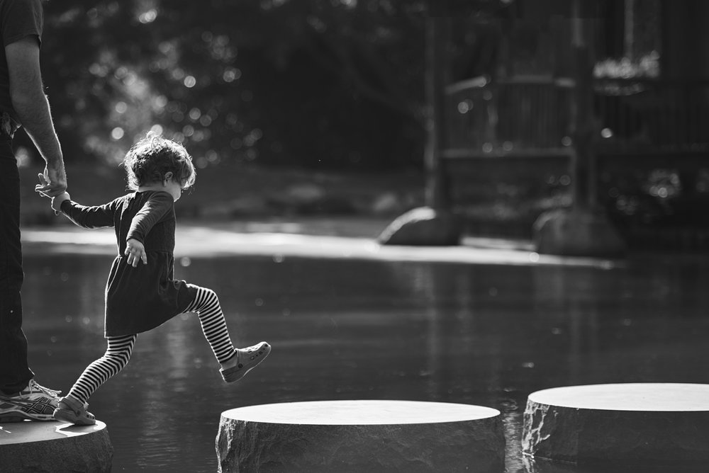 Manhattan, KS Family photographer takes picture of little girl jumping stones while holding dads hand.