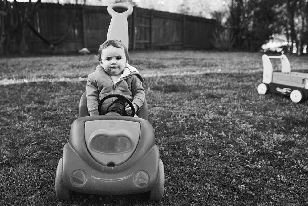 In home documentary family photographer captures skeptical look from the youngest at their Riley County Family home.